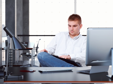 white color worker: Young casual caucasian business office worker reading ebook on tablet, sitting at desk, looking at screen, legs crossed. Unsmiling,