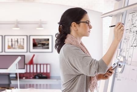 Axé femme architecte caucasien occasionnels travaillant à la planche à dessin à la plume à la main. Le port de lunettes, au bureau. Le plan d'étage, occupé, la concentration, sans sourire.
