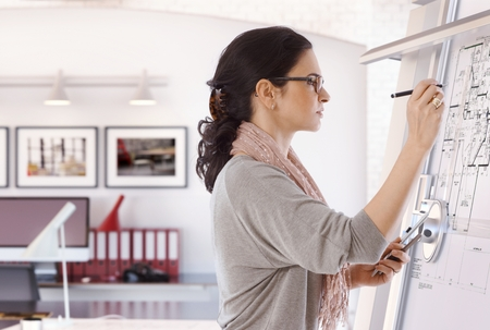 Focused casual caucasian female architect working at drawing board with pen in hand. Wearing glasses, at office. Floor plan, busy, concentration, unsmiling. Stock Photo