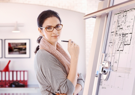 architect office: Casual female caucasian architect standing at drawing board and floor plan with pencil in hand at office. Wearing glasses, smiling, looking at camera.