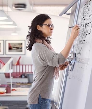 Casual Kaukasische medio volwassen vrouw bezig tekeningpakket bij architect kantoor op tekentafel. Pen in de hand, dragen van een bril, staande. Geconcentreerd, concentratie. Stockfoto