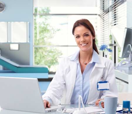 Happy female caucasian doctor at office sitting in front of laptop computer desk, wearing lab coat, indoors. Smiling, looking at camera, name tag. photo