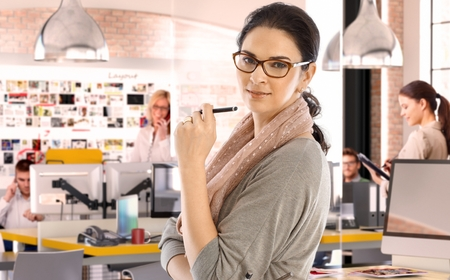 startup: Casual caucasian businesswoman at business startup office with pen in hand, wearing glasses. Looking at camera, scarf around neck.