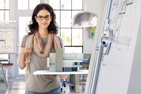 女性のカジュアルな白人建物モデル手で押し、立ち、笑みを浮かべて、カメラ目線でデザイナーの建築家します。明るいオフィス。