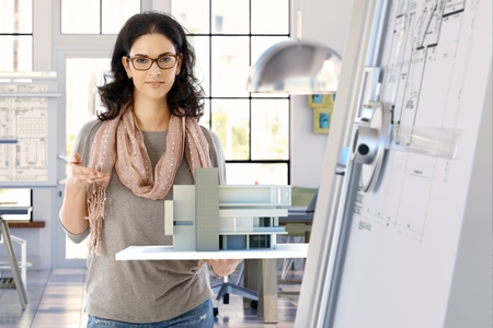 Female casual caucasian architect designer with building model holding in hand, standing, smiling, looking at camera. Bright office. Banque d'images