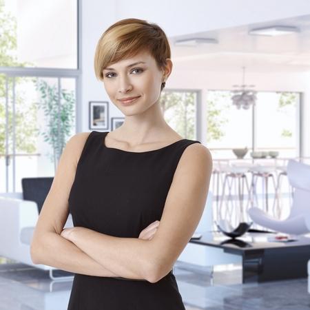魅力的なカジュアルな白人若い実業家デザイナー家で腕を組んで、笑みを浮かべて、カメラを見て立っています。