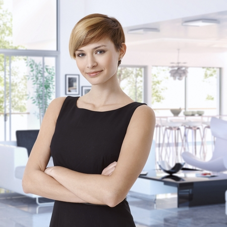 Attractive casual caucasian young businesswoman at designer home, standing, arms crossed, smiling, looking at camera.