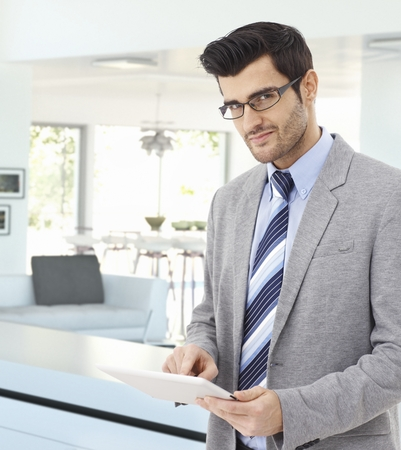 bristly: Handsome caucasian businessman at home with tablet in hand, wearing suit and glasses, standing, smiling, looking at camera. Pointing, bristly, business.