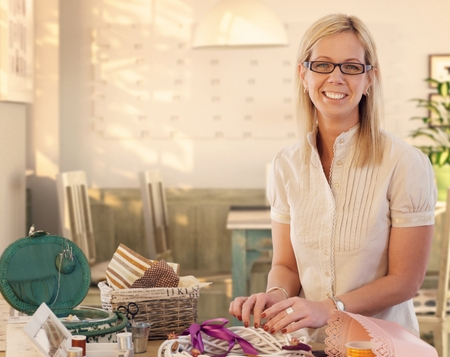 blonde females: Happy casual caucasian blonde mid adult businesswoman making valentine day wreath at home. Smiling, wearing glasses, standing at table, do it yourself, gift, present. Looking at camera.