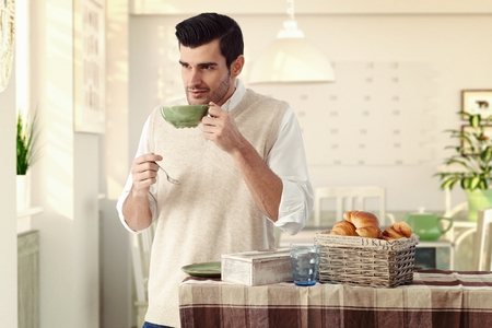bristly: Handsome casual caucasian man drinking morning breakfast tea at vintage home with tea cup and spoon in hand. Wearing sleeveless sweater, standing at dining room, wondering, thinking, smiling, bristly. Stock Photo