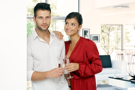 Attractive young casual romantic couple at home with champagne glass in hand. Standing, leaning against wall. Handsome man and attractive woman in red dressing gown, smiling. photo