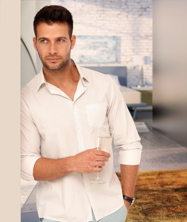 stubble: Handsome serious casual caucasian man with a glass of champagne at designer home. Unsmiling, standing against wall, hand in pocket.