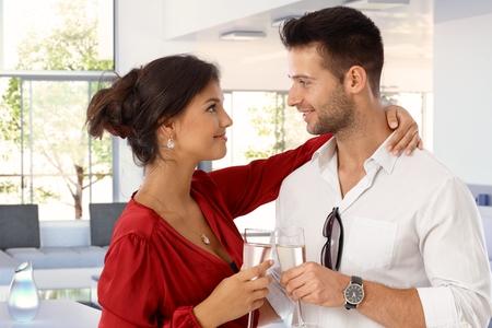 Glücklich romantische junge caucasian Paar mit Champagner zu Hause. Attraktive Frau und gut aussehend Mann klirrende Gläser. Lächeln Stehen, Umarmen, Augenkontakt.
