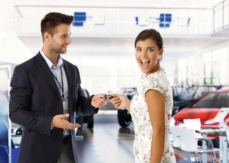 Excited attractive young caucasian lady is getting keys for new car from salesman at car dealership business saloon. Handsome man wearing suit and attractive woman, standing, looking at camera, mouth open.