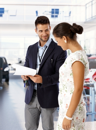 Satisfied caucasian young salesman wearing suit at new car dealership saloon with keys and business papers. Standing, looking at happy female customer. photo