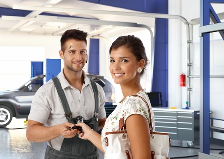 Happy attractive caucasian young lady at auto repair shop, getting car keys back from handsome dirty male mechanic. Smiling standing looking at camera.