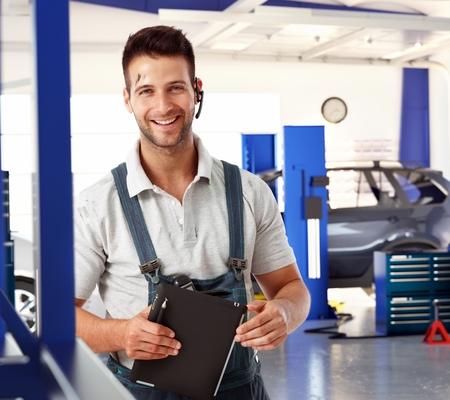 Gelukkig knappe blanke mannelijke automonteur bij auto reparatie bedrijf winkel. Het dragen van werkkleding kleding en draadloze headset, glimlachen, staand, kijkend naar de camera. Vettige, vuile, tablet computer in de hand.