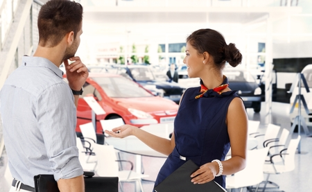 Female caucasian business sales representative at car saloon dealership with male client, presenting new automobile. Gesturing, standing, smiling in formal dress, looking away.