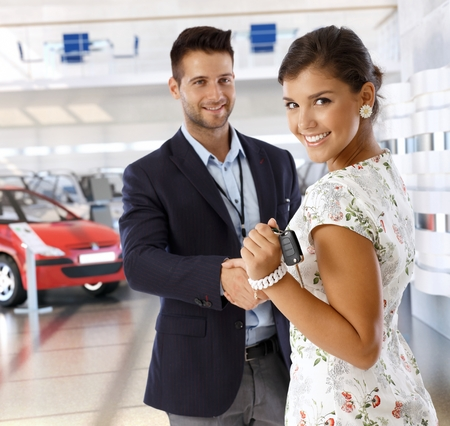 handing over: Attractive young caucasian casual businesswoman shaking hands with car dealer wearing suit at business dealership saloon, Looking at camera, smiling, standing, handing over keys.