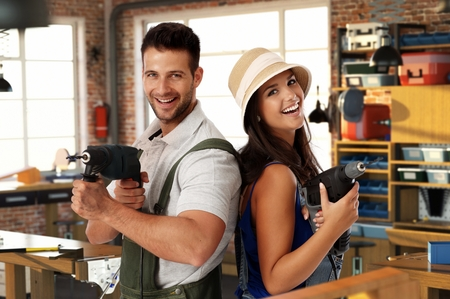 Happy young caucasian casual couple having fun at home workshop. Smiling, looking at camera, holding power drill in hand, standing. Handsome man, attractive female. Do it yourself. Stock Photo