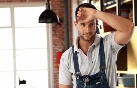 bristly: Handsome casual tired bristly caucasian handyman at workshop. Standing in workwear, wearing wireless headset hand wiping brow. Do it yourself. Stock Photo
