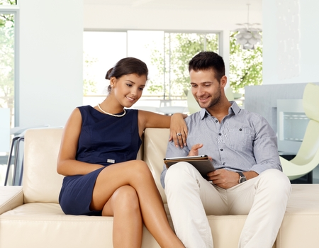 Young caucasian couple at home browsing internet with tablet computer while sitting on sofa. Smiling, pointing at screen, attractive woman. photo
