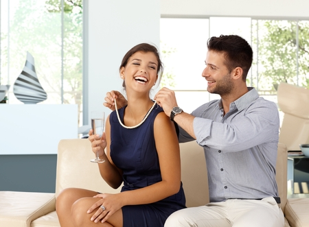 romance: Felice donna caucasica con champagne in mano ottenendo regalo collana di perle da marito. Coppia felice, seduto a casa sul divano in salotto, romanticismo, gioielli.