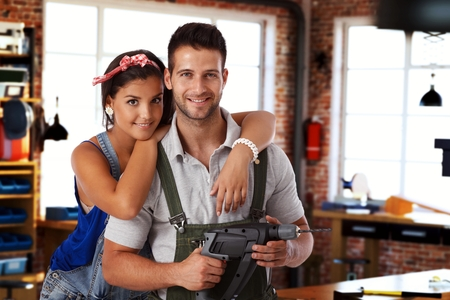 Happy young caucasian couple standing at home workshop, looking at camera, hugging, smiling. Power drill in hand. photo