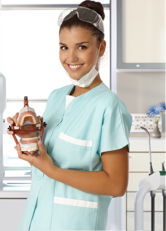 Attractive young dental assistant smiling happy, holding dentures in hand. photo