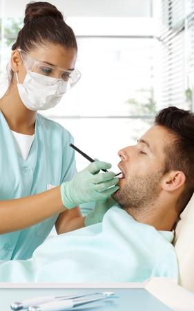 Female dentist examining patient. photo