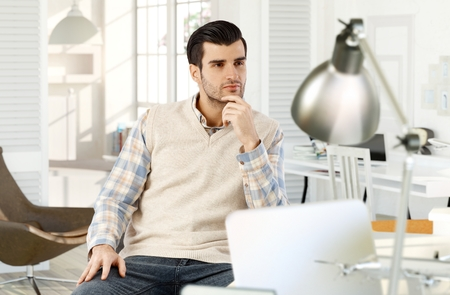 Young man sitting at home, daydreaming, hand on chin. Stock Photo