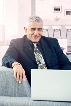 Portrait of happy senior businessman smiling, having laptop. photo