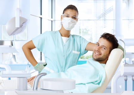 odontology: Dental surgeon and patient smiling happy after dental checkup, looking at camera. Stock Photo
