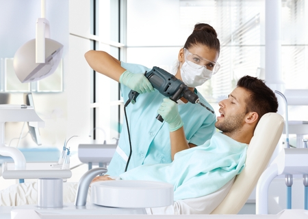 Aggressive female dentist using power drill for drilling patients tooth. Stock Photo