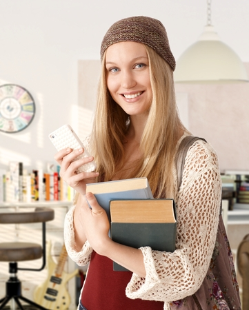 Portrait of happy blonde college student holding books, using mobile, looking at camera. photo