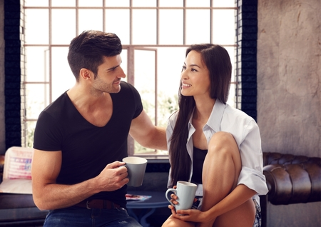 asian american: Attractive loving couple drinking tea at home, talking.