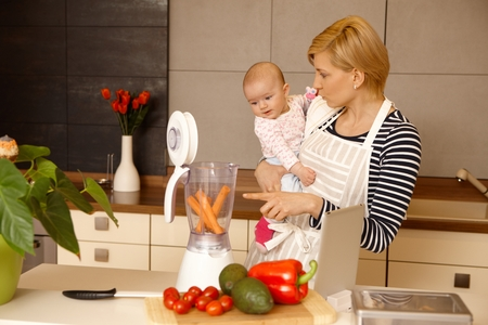 Young mother holding baby girl in arms, preparing food together in kitchen. photo