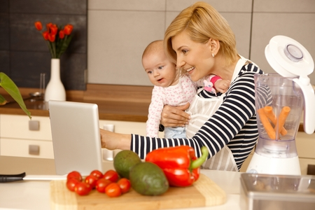 Moeder en baby meisje met behulp van laptop computer in de keuken, het koken.
