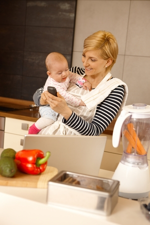 Young woman working from home while holding baby in arms. photo