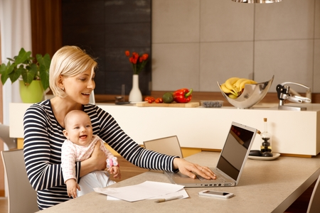 Young woman working at home with computer, holding baby girl in arms. Stock Photo