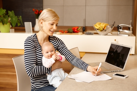 blonde mom: Young woman working from home, holding baby girl on lap.