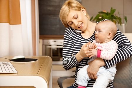 Young woman talking on mobile holding baby on lap. photo