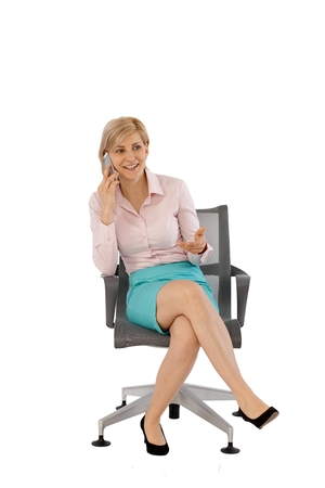 Businesswoman talking on mobilephone, sitting in swivel chair, smiling. Full size, white background.