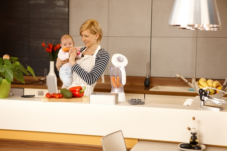 MOther holding baby girl in kitchen. Baby eating carrot. photo