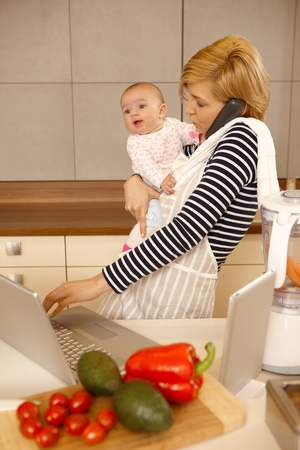 Young woman holding baby in arm, talking on phone, using laptop and tablet in kitchen. photo