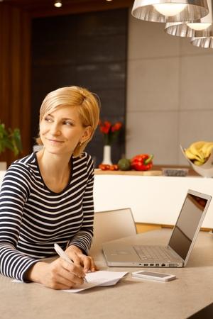 Glückliche junge Frau arbeitet zu Hause, sitzt am Tisch und schrieb.