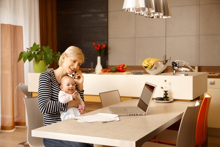 Junge Unternehmerin arbeitet zu Hause, hält Baby auf dem Schoß.