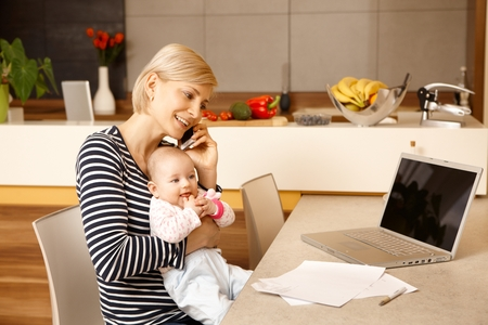 Young mother working from home, holding baby on lap. photo
