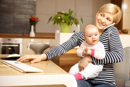 Businesswoman working from home, holding baby girl on lap.