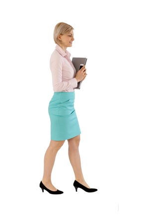 Businesswoman walking with folder in hand over white background. Full size, side view.